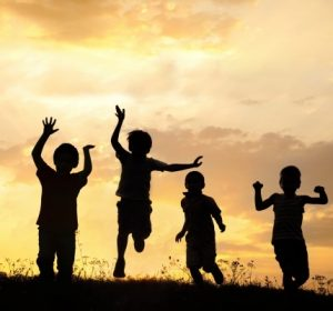 Silhouette group of happy children playing on meadow sunset